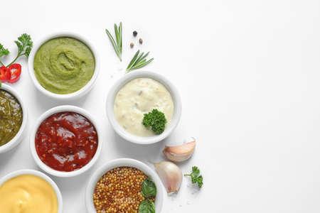 Composición con diferentes salsas e ingredientes sobre fondo blanco, plano laical. Espacio para texto