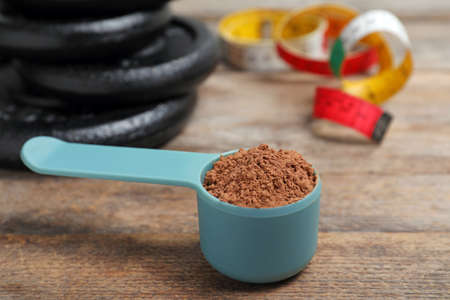 Scoop with protein powder, measuring tape and dumbbell plates on wooden table. Space for text Stock Photo