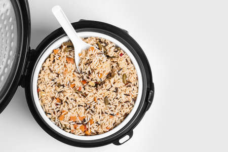 Delicious rice with vegetables and spoon in modern multi cooker on white background, top view