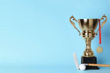Goldener Trophäenpokal, Medaille, Golfclub und Ball auf farbigem Hintergrund. Platz für Text