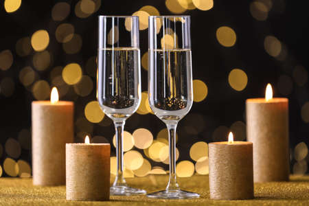 Champagne glasses and golden candles on table against defocused lights