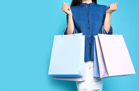 Woman with blank paper bags against color background, closeup. Space for text