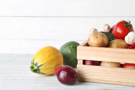 Wooden crate full of fresh vegetables on table. Space for text 写真素材