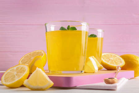 Glasses of lemon jelly served on light wooden table against color background