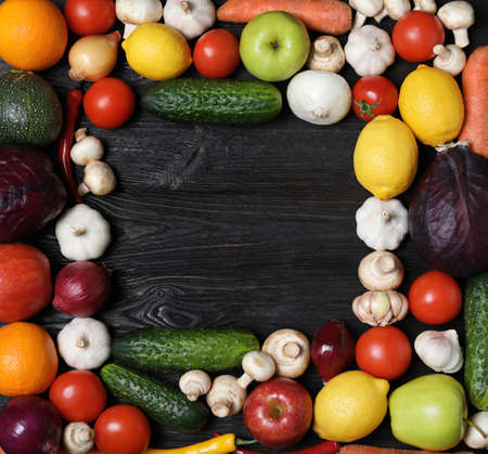 Frame made of fresh delicious vegetables and fruits on wooden table, flat lay. Space for text