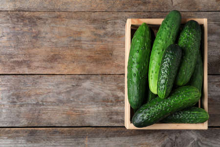 Crate full of fresh ripe cucumbers on wooden background, top view. Space for text