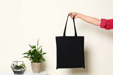 Woman with stylish blank eco bag  near white wall, closeup. Space for text Imagens - 124978004