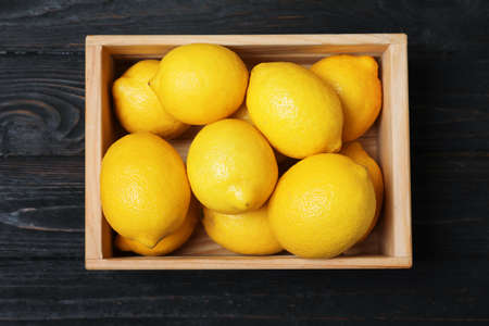 Wooden crate full of fresh lemons on dark background, top view Stock Photo