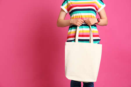 Woman with stylish blank eco bag against color background, closeup. Space for text Imagens - 124978831