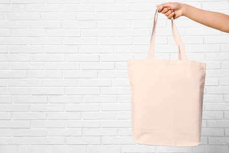 Woman with stylish blank eco bag near brick wall, closeup. Space for text Imagens - 124978953