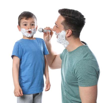 Dad applying shaving foam onto son's face against white background