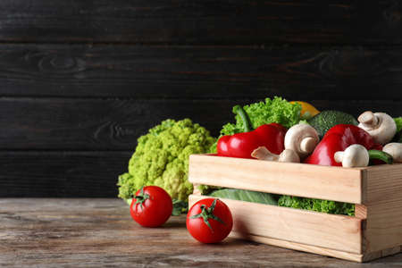 Wooden crate full of fresh ripe vegetables on table. Space for text