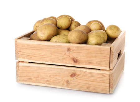 Wooden crate full of fresh raw potatoes on white background
