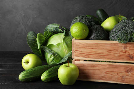 Wooden crate, fresh green fruits and vegetables on dark background