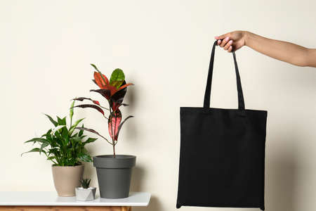 Woman with stylish blank eco bag against color background, closeup Imagens