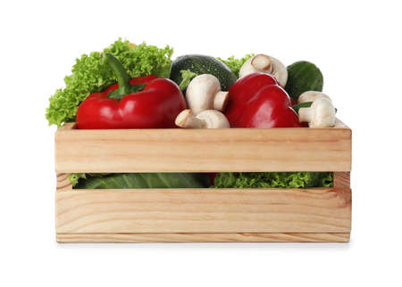 Wooden crate full of fresh ripe vegetables on white background