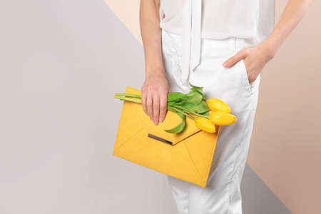Stylish woman with clutch and spring flowers against color background, closeup. Space for text