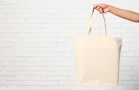 Woman with stylish blank eco bag near brick wall, closeup. Space for text Imagens - 124979427