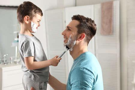 Little son shaving his dad in bathroom
