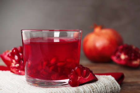 Glass of pomegranate jelly served on table, closeup. Space for text