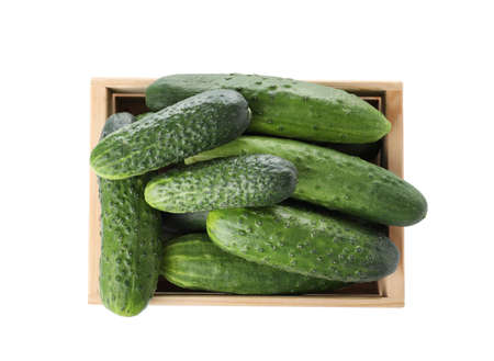 Wooden crate full of fresh ripe cucumbers on white background, top view