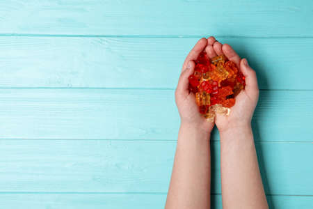 Woman with colorful jelly bears on wooden background, top view. Space for text