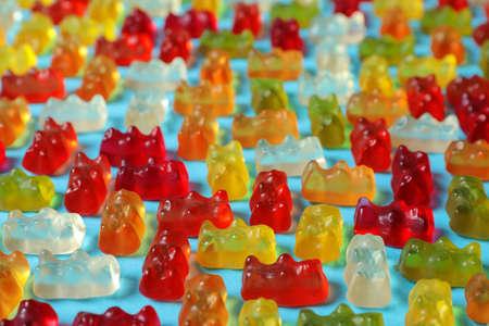 Flache Laienzusammensetzung mit köstlichen Gummibärchen auf farbigem Hintergrund
