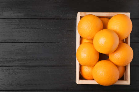 Wooden crate full of fresh oranges on dark background, top view. Space for text