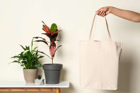 Woman with stylish blank eco bag against color background, closeup Imagens - 124979566