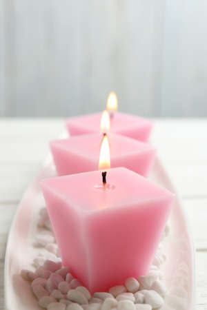 Composition with three burning candles on white table
