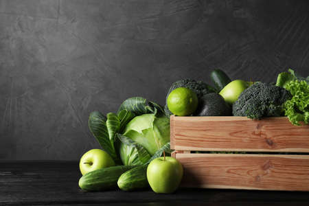 Wooden crate, fresh green fruits and vegetables on dark background. Space for text