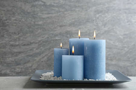 Plate with burning candles and rocks on table, space for text Stock Photo