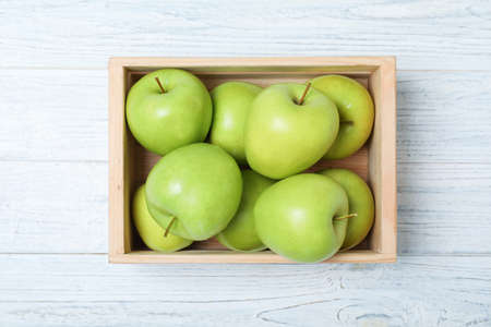 Wooden crate full of fresh green apples on light background, top view