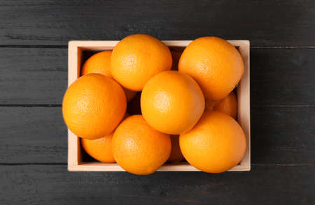 Wooden crate full of fresh oranges on dark background, top view Stock Photo