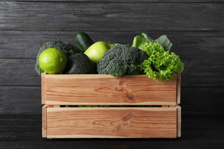 Wooden crate full of fresh green fruits and vegetables on dark background