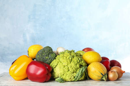 Variety of fresh delicious vegetables and fruits on table against color background
