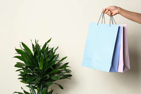Woman with blank paper bags against color background, closeup. Space for text Imagens - 124986239