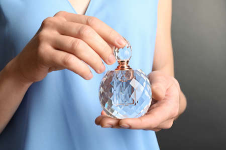 Woman holding glass perfume bottle, closeup view