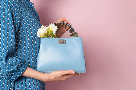 Stylish woman with handbag and spring flowers against color background, closeup. Space for text 版權商用圖片