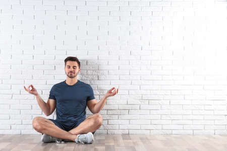 Handsome young man sitting on floor and practicing zen yoga near brick wall, space for text