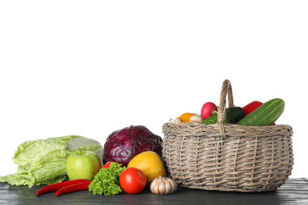 Wicker basket with variety of fresh delicious vegetables and fruits on table against white background