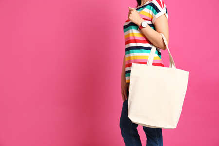Woman with stylish blank eco bag against color background, closeup. Space for text