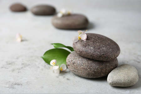 Spa stones with flowers and leaves on grey table. Space for text