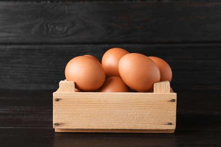 Wooden crate full of fresh eggs on dark background Stock Photo