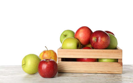 Wooden crate full of fresh juicy apples on table against white background