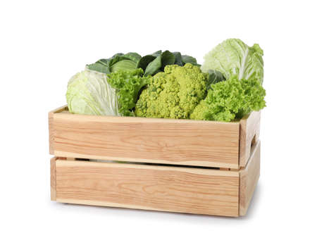 Wooden crate full of fresh green vegetables on white background