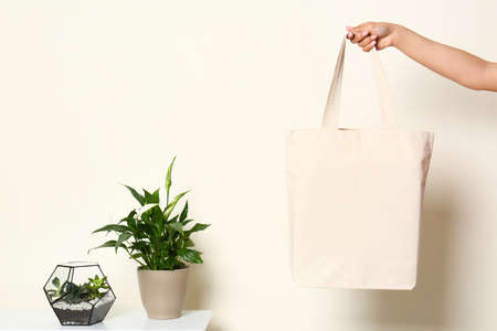 Woman with stylish blank eco bag near white wall, closeup. Space for text Reklamní fotografie