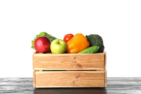 Wooden crate filled with fresh vegetables and apples on table against white background Banque d'images