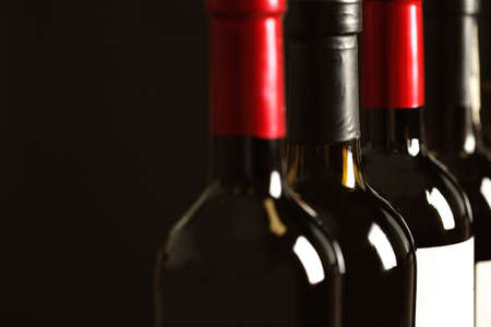 Bottles of different wines on dark background, closeup. Expensive collection Imagens