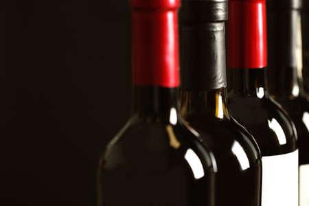 Flessen verschillende wijnen op donkere achtergrond, close-up. Dure collectie Stockfoto